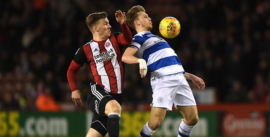 Luke Freeman shields the ball from Lee Evans