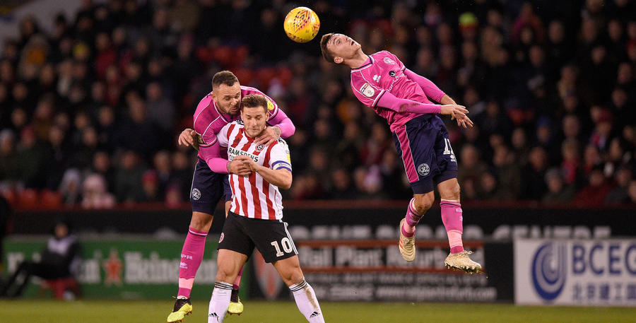 Josh Scowen gets his head to the ball as Joel Lynch tussles with Billy Sharp