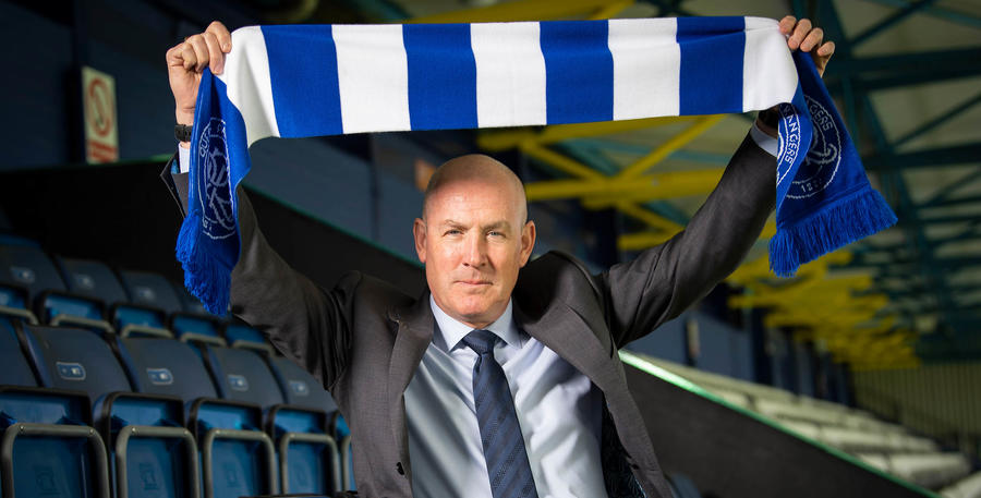 The gaffer holds a scarf aloft in the Loftus Road stands